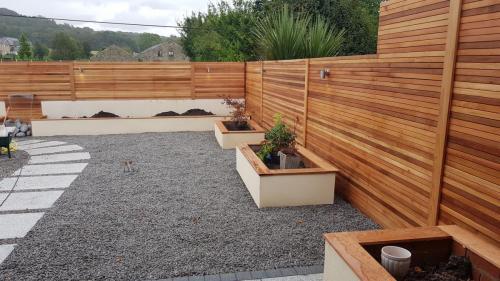 garden landscaping pebbles red cedar wood sleeper border planting